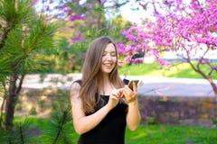 Fille gaie à l'aide du smartphone dans le jardin avec le fond de fleur Photo libre de droits