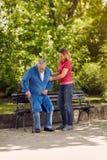 Fille gaie aidant le père handicapé en parc Image libre de droits
