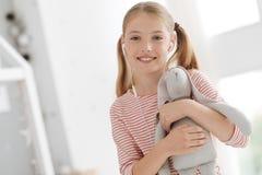Fille gaie avec des écouteurs embrassant le jouet de lapin Photo stock
