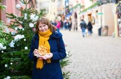 Fille gaie avec le bretzel sur le marché de Noël Photo stock
