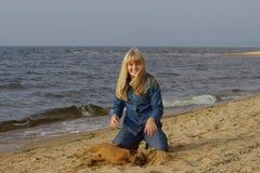 Fille gaie avec un chien par la mer Photos libres de droits