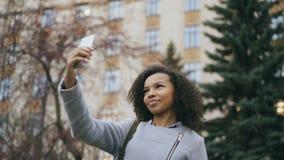 Fille gaie d'étudiant d'afro-américain parlant à l'appel visuel avec le smartphone près de l'univercity banque de vidéos