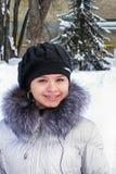 Fille gaie dans la neige sur un fond des arbres Photos stock