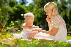 Fille gaie et garçon mangeant des bonbons en parc image libre de droits