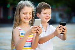 Fille gaie et garçon regardant des téléphones portables en parc Photos stock