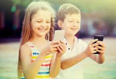 Fille gaie et garçon regardant des téléphones portables en parc Image stock