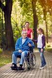 Fille gaie et petits-enfants rendant visite au père handicapé dedans photo libre de droits