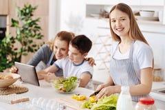 Fille gaie faisant cuire la salade végétale dans la cuisine Image libre de droits