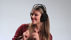 Fille gaie heureuse appréciant la musique dans des écouteurs clips vidéos
