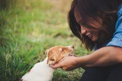 Fille gaie heureuse de hippie jouant avec son chien dans le dur de parc Photos stock