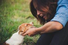 Fille gaie heureuse de hippie jouant avec son chien dans le dur de parc Images stock