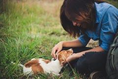 Fille gaie heureuse de hippie jouant avec son chien dans le dur de parc Photos libres de droits