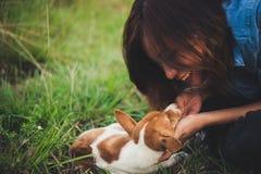 Fille gaie heureuse de hippie jouant avec son chien dans le dur de parc Photo stock