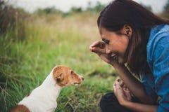 Fille gaie heureuse de hippie jouant avec son chien dans le dur de parc Image stock