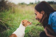 Fille gaie heureuse de hippie jouant avec son chien dans le dur de parc Photographie stock