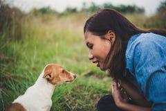 Fille gaie heureuse de hippie jouant avec son chien dans le dur de parc Photo libre de droits
