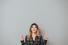 Fille gaie heureuse dirigeant deux doigts à l'espace de copie Images stock