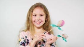 Fille gaie jouant avec des oeufs ouvrant des yeux stupéfaits Danse mignonne de fille avec des oeufs de pâques sur des bâtons banque de vidéos