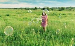 Fille gaie jouant parmi des bulles de savon en été Photo stock