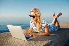 Fille gaie mentant à l'été sur la plage près de la mer et aux entretiens à Images stock
