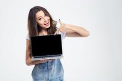 Fille gaie montrant l'écran vide d'ordinateur portable Photographie stock libre de droits