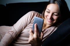 Fille gaie observant l'affichage futé de téléphone la nuit images libres de droits