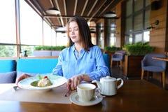 Fille gaie passant en revue par le smartphone au café et mangeant le desser photographie stock libre de droits