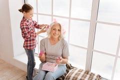 Fille gaie positive à l'aide des rouleaux de cheveux Photos stock