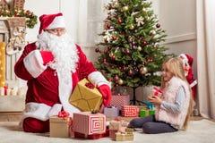 Fille gaie recevant le cadeau de Noël de Santa Photographie stock