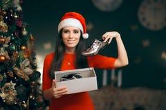 Fille gaie recevant les chaussures plates argentées comme cadeau de Noël photos stock