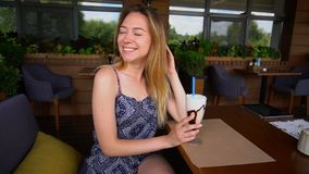 Fille gaie s'asseyant au café avec le cocktail de crème glacée et regardant l'appareil-photo dans le mouvement lent banque de vidéos