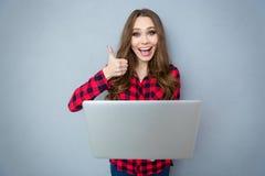 Fille gaie tenant l'ordinateur portable et montrant le pouce  Photographie stock libre de droits