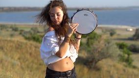 Fille gitane bouclée de brune jouant sur le tambour de basque dans le domaine sur la pente du Golfe clips vidéos