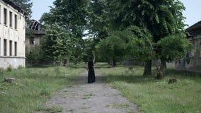 Fille gothique avec de longs cheveux et une robe noire marchant entre de vieux bâtiments abandonnés clips vidéos