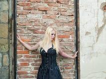 Fille gothique blonde devant un mur de briques Photos libres de droits