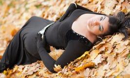 Fille gothique dans les feuilles Photographie stock