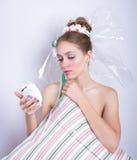 Fille-guimauve avec un oreiller et un réveil dans des ses mains Image stock