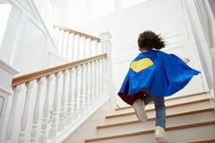 Fille habillée vers le haut de comme le super héros jouant le jeu sur des escaliers Photographie stock libre de droits