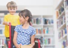 Fille handicapée dans le fauteuil roulant avec l'ami dans la bibliothèque d'école Images stock