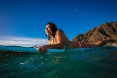 Fille hawaïenne de surfer dans l'eau sur son conseil surfant photographie stock libre de droits