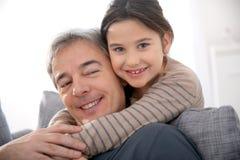 Fille heureuse étreignant son père de sourire Photo libre de droits