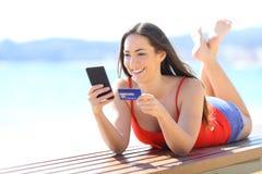 Fille heureuse achetant en ligne avec le téléphone et la carte de crédit photos stock
