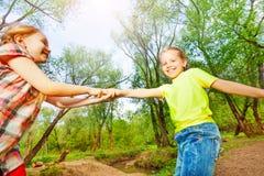 Fille heureuse aidant son ami obtenant au-dessus de la rivière Images stock