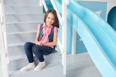 Fille heureuse 7 ans se reposant sur les escaliers Images stock