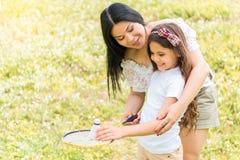 Fille heureuse apprenant le jeu de tennis avec l'aide de mère Photos libres de droits