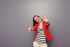 Fille heureuse attirante montrant des pouces vers le haut Images libres de droits