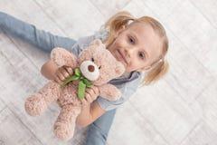 Fille heureuse attrayante ayant l'amusement avec l'ours de peluche Photos libres de droits