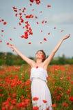 Fille heureuse avec augmentés les bras dans le domaine vert des fleurs Concep Image stock