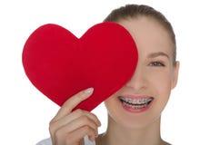 Fille heureuse avec des accolades sur les dents et le coeur Photographie stock libre de droits