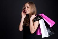 Fille heureuse avec des achats parlant sur le téléphone portable Image stock